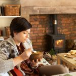 Young woman having tea by fire